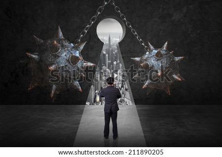 difficult path of businessman front of spike wrecking ball against keyhole exit to urban scene balcony over looking city dusky in concept of obstacle and trap on the way of a business  - stock photo
