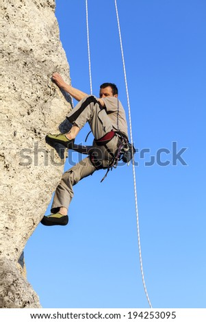 Difficult rock climbing position on horizontal cliff, mountains in Poland.
