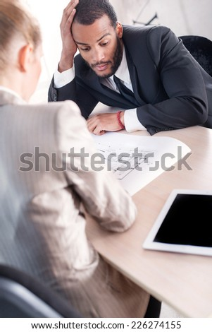 Difficult task for the project. Successful African businessman considering a project while the second businessman sitting next to a table and holding a document in his hand