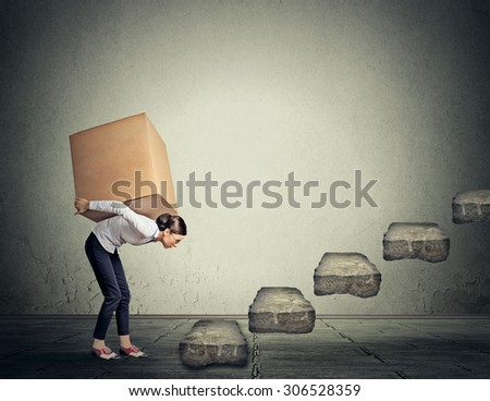 Difficult task perspective concept. Young slim woman entrepreneur carrying large heavy box on her back upstairs - stock photo