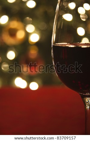 Diffused lights and ornaments from a Christmas tree form the background for a close-up of a glass of red wine.