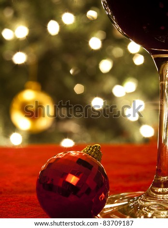 Diffused lights and ornaments from a Christmas tree form the background for a close-up of a glass of red wine and a red ornament. - stock photo