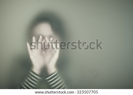 Diffused silhouette of woman through frosted glass - stock photo