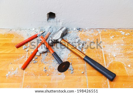 Dig or drill a hole in the cement wall using cold chisels and hammer  - stock photo