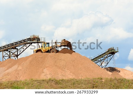 Digger and conveyor belts making piles of earth at quarry - stock photo
