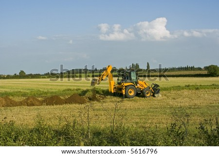 digger in countryside digging holes in the ground - stock photo