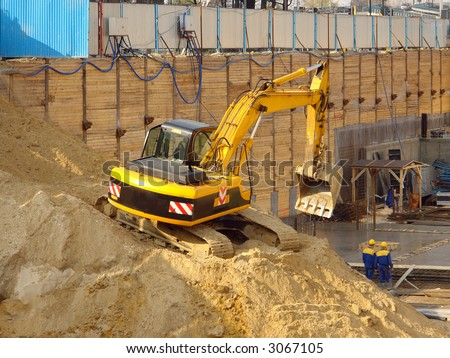 Digger working on a heap of sand inside giant foundation excavation - stock photo