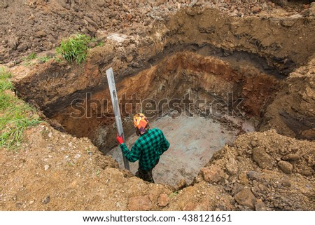 digging and leveling the bottom of the backyard septic tank outflow - stock photo