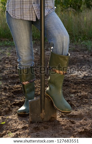 digging in green boots, close-up - stock photo