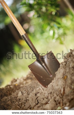 Digging spring soil with shovel. Close-up, shallow DOF. - stock photo