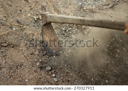 Digging the soil with a hoe to make the garden ready. Note : Motion blur for dynamic of scene - stock photo