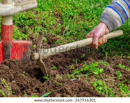 Digging With  hoe in garden - stock photo