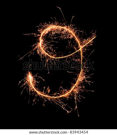 Digit 9 made of sparklers isolated on black