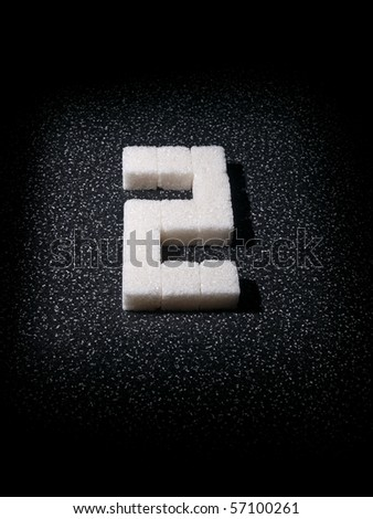 Digit two built from lumps sugar in dark tone - stock photo