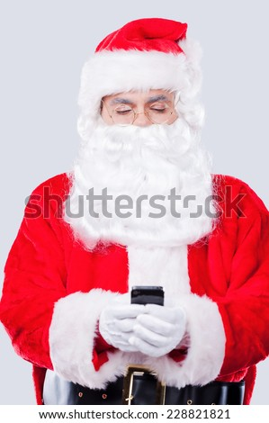 Digital age Santa. Traditional Santa Claus holding mobile phone while standing against grey background