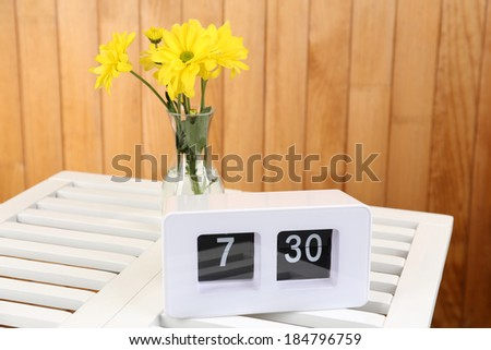 Digital alarm clock on table, on wooden background - stock photo