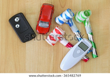 Digital alcohol breath tester device in white next to a car remote key and colorful party horns - stock photo
