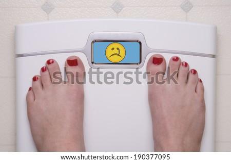 Digital Bathroom Scale Displaying a Sad Emoji - stock photo
