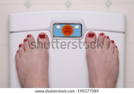 Digital Bathroom Scale Displaying an Angry Emoji - stock photo