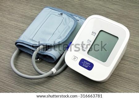 Digital Blood Pressure Monitor on wood background, Medical equipment, Examining equipment. - stock photo