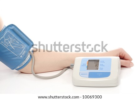 Digital blood pressure monitor put on female hand showing normal blood pressure parameters - shot over white background - stock photo