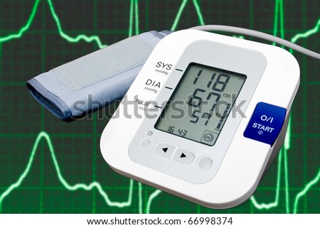 Digital blood pressure monitor with cardiogram in the background - stock photo
