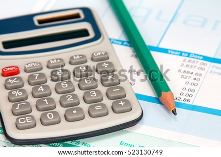 Digital calculator and pencil on the statement of payroll details