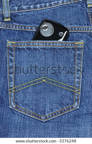 Digital camera lens of pda phone in blue jeans pocket - stock photo