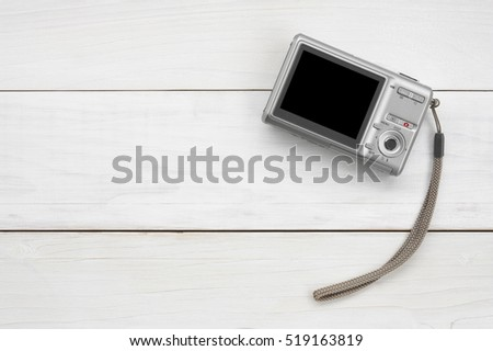 digital compact camera with blank black screen display and hand strap on white vintage wood table top view with copy space, included clipping path for compact camera black screen display
