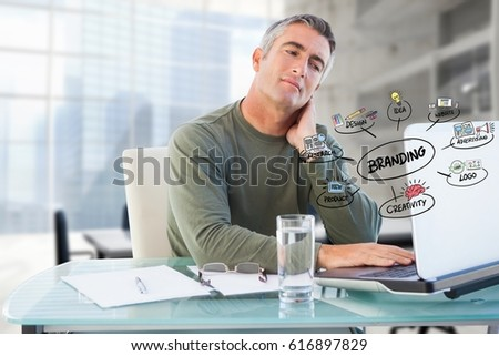 Digital composite of Businessman using laptop with colorful business branding doodles in office