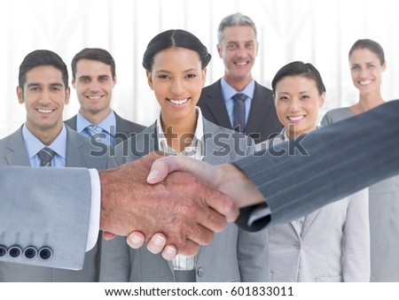 Digital composite of Handshake in front of business people in office against white background