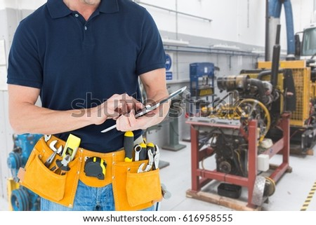 Digital composite of Midsection of handyman using tablet PC at workshop