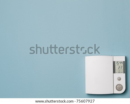 Digital control home thermostat on blue wall - stock photo