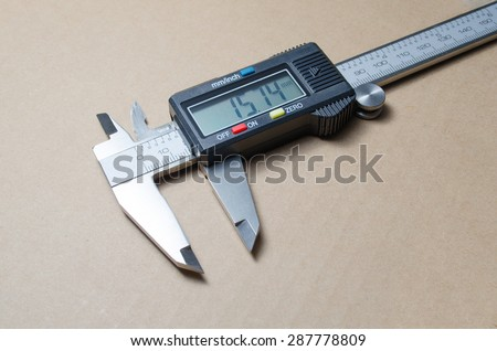 Digital electronic vernier caliper on a brown background - stock photo