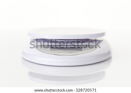 Digital food scale electronic weight balance on white backgroound. - stock photo