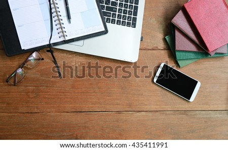 Digital gadgets with daily notebook and laptop on the wooden table. Top view,Layout of comfortable working space on wooden, internet laptop headphone phone notepad pen eyeglasses laying on it - stock photo