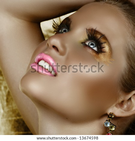 Digital manipulation of a beautiful woman with fantasy golden make-up and good skin texture and pore definition - stock photo