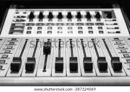 digital music studio mixer, shallow dept of field & focus on third track fader for recording or TV / radio broadcast background concept = you can be the leader in your business