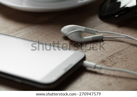 digital music white Headphones among a smart phone and a cup of coffe - stock photo
