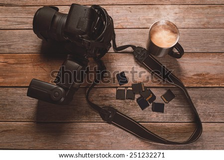 Digital photo camera, memory cards and cup of coffee on wooden table - stock photo