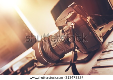 Digital Photography Workstation. Modern Digital DSLR Camera, Laptop Computer and Display. - stock photo