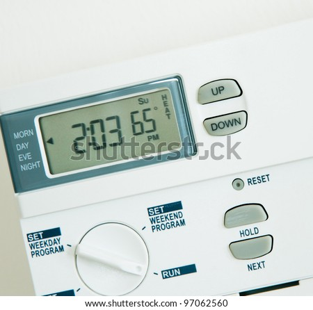 Digital programmable Thermostat at 65 degree heat isolated on White background - stock photo