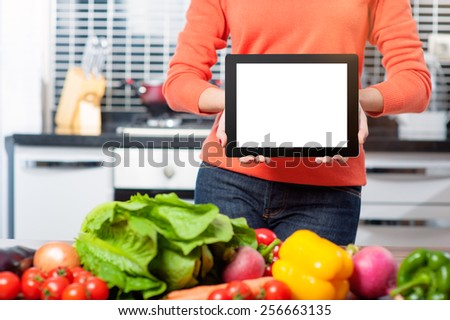 digital recipes book. Cheerful young woman holding digital tablet standing in her kitchen at home - stock photo