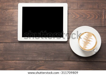 Digital tablet and coffee cup on wooden background. - stock photo