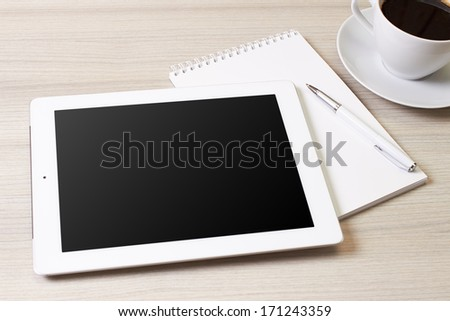 digital tablet and cup of coffee on wooden table - stock photo