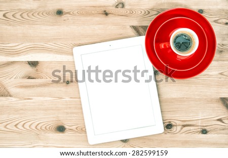 Digital tablet and cup of coffee on wooden table. Home office workplace. Vintage style toned picture - stock photo