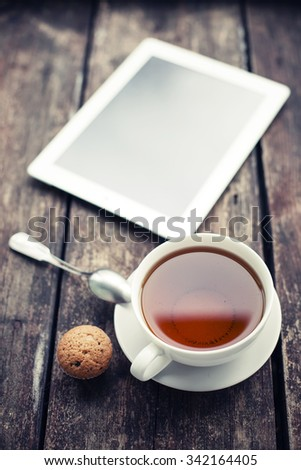 Digital tablet and cup of tea on old wooden desk. Simple workspace in morning/ selective focus - stock photo
