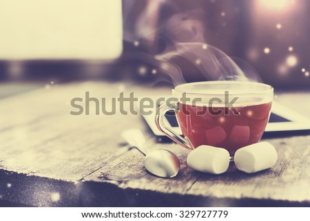 Digital tablet and cup of tea on old wooden desk. Simple workspace or coffee break in winter morning/ selective focus - stock photo