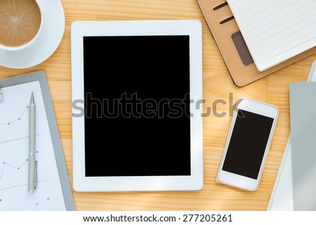 Digital tablet and smartphone on the table of businessperson, view from above