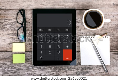 digital tablet as a calculator  and coffee cup wit  on wooden table - stock photo